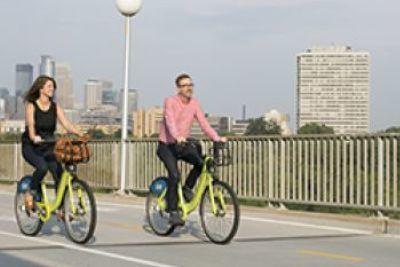 Couple rides bikes along U of M bridge
