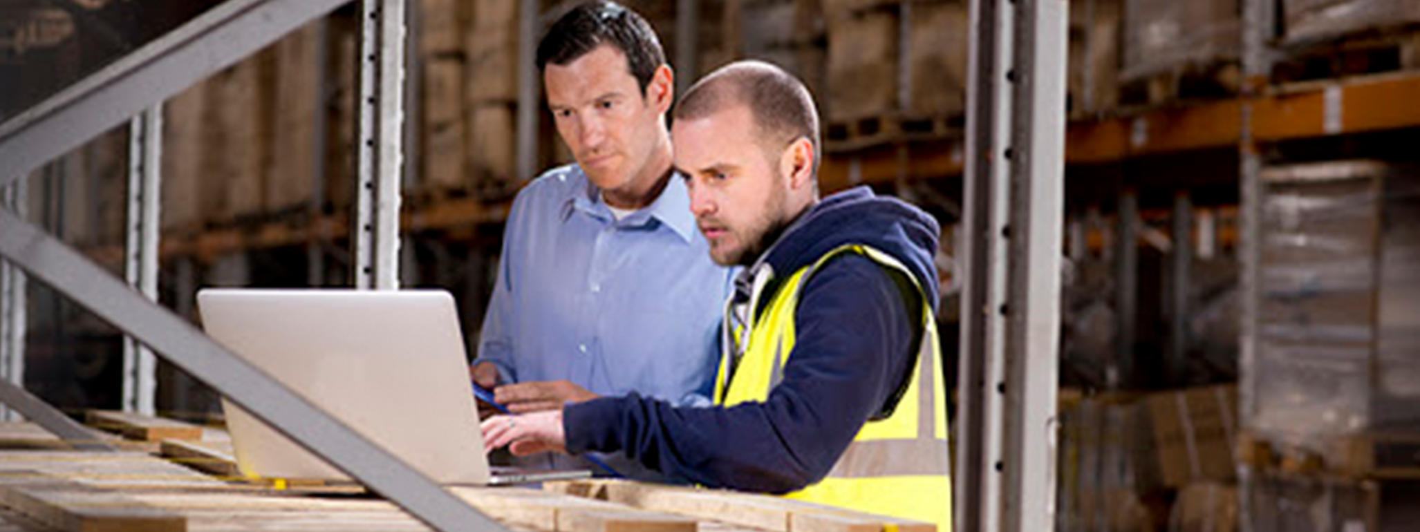 This image shows two men looking at a laptop inside of a warehouse. The man on the left is wearing a blue button down, and the man on the right is wearing a reflective vest. They are both looking at the computer screen.