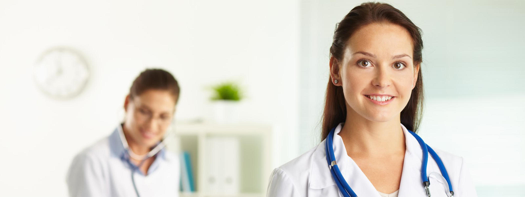 This image shows two female nurses. The nurse on the left is slightly blurry and further in the background using a stethoscope. The nurse on the right is in the forefront smiling and wearing a stethoscope.